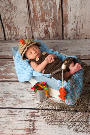 Portrait of a nine day old newborn baby boy. He is sleeping in a miniature boat and wearing crocheted overalls and a fisherman's hat. Shot in the studio on a rustic wood background.