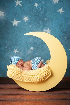 Studio portret van een negen dagen oude baby jongetje draagt pyjamabroek en een slaapmuts. Hij slaapt op een maanvormige poseren prop.