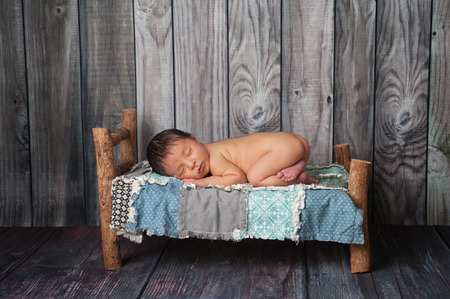 he: Portrait of a nine day old newborn baby boy. He is sleeping on a miniature bed with a patchwork quilt. Shot in the studio on a rustic wood background. Stock Photo
