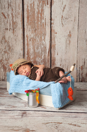 siesta: Portrait of a nine day old newborn baby boy. He is sleeping in a miniature boat and wearing crocheted overalls and a fishermans hat. Shot in the studio on a rustic wood background. Stock Photo