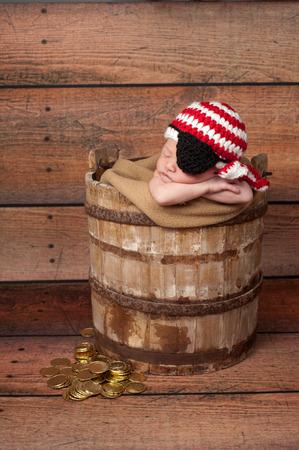 sombrero pirata: Una semana de edad ni�o reci�n nacido beb� que llevaba un sombrero de pirata de punto rojo y blanco y parche en el ojo negro �l est� durmiendo en una, de madera, as� balde r�stico