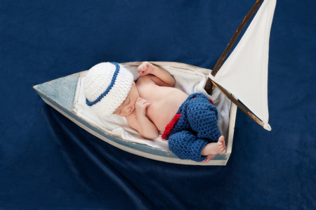 One week old newborn baby boy wearing a white and blue sailor hat. It is an overhead view of him sleeping contentedly on his back in a little sailboat. Shot in the studio on navy blue velvet.