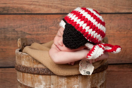 he old: One week old newborn baby boy wearing a crocheted red and white pirate hat and black eye patch. He is sleeping in a rustic, wooden, well bucket and holding a tiny treasure map.  Stock Photo