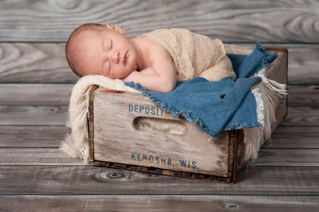 One week old newborn baby boy sleeping on his stomach in a vintage, wooden soda pop crate lined with frayed burlap and denim. Shot in the studio on rustic wood background. Stock Photo