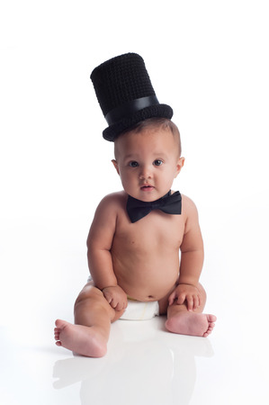 A portrait of a seven month old, Hispanic baby boy wearing a diaper, top hat and bow tie  He is sitting and looking at the camera  Shot in the studio and isolated on a white background  photo