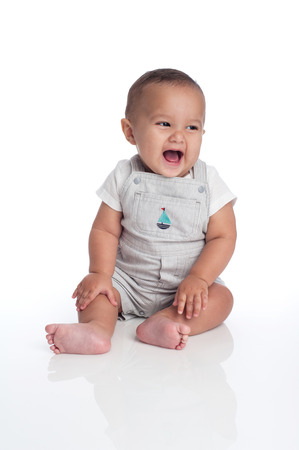 A portrait of a seven month old, hispanic baby boy laughing  He is wearing overalls with a sailboat decal and looking of to the side  Shot in the studio and isolated on white  Stock Photo