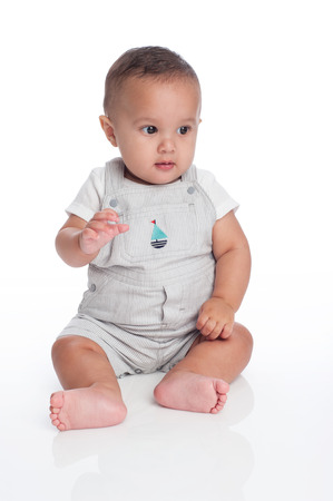 6 12: A portrait of a seven month old, hispanic baby boy  He is wearing overalls with a sailboat decal and looking of to the side  Shot in the studio and isolated on white