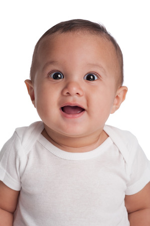 A portrait of a seven month old, Hispanic baby boy with a surprised, happy expression  He is wearing a white onesy and looking at the camera  Shot in the studio and isolated on white  Stock Photo