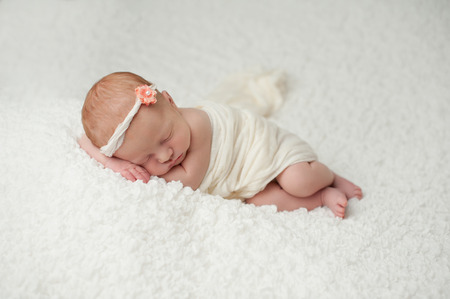 Portrait of a red headed, 2 week old, newborn baby girl  She is wrapped in white material and sleeping on a white, gauzy blanket  Archivio Fotografico