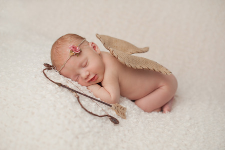Portrait of a smiling, red headed, 2 week old, newborn baby girl  She is wearing a Cupid costume with angel wings, bow and arrow and is sleeping on a cream colored blanket