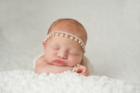 Portrait of a red headed, 2 week old, newborn baby girl  She is wearing a rhinestone and pearl headband and bracelet and is sleeping on a white, gauzy blanket
