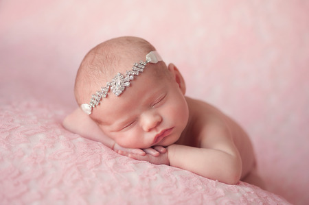 Portrait of 10 day old newborn baby girl. She is wearing a rhinestonel headbandand is sleeping on light pink lace material.