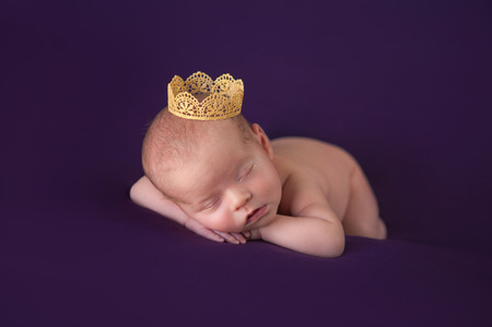 Portrait of 10 day old newborn baby girl. She is wearing a gold crown and is sleeping on dark purple material.
