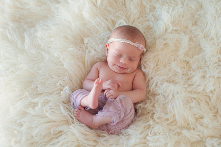 Beautiful portrait of a smiling 10 day old newborn baby girl. She is curled up and asleep on her back on a cream colored flokati rug.