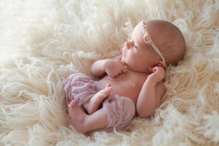 Beautiful portrait of an alert 10 day old newborn baby girl. She is awake and curled up oon her back on a cream colored flokati rug.