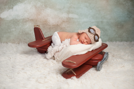Studio portrait of an eight day old newborn baby boy wearing an aviator cap with goggles. He is sleeping on a vintage inspired airplane posing prop.