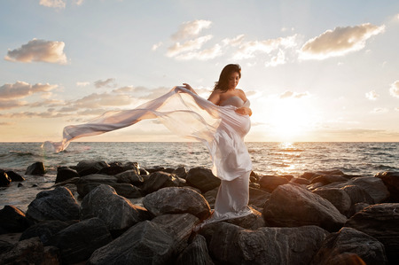 A beautiful pregnant woman on a rocky beach at sunrise. She is holding a gray silk veil that Stockfoto
