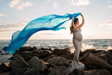 A beautiful, smiling pregnant woman on a rocky beach at sunrise. She is holding a blue silk veil that