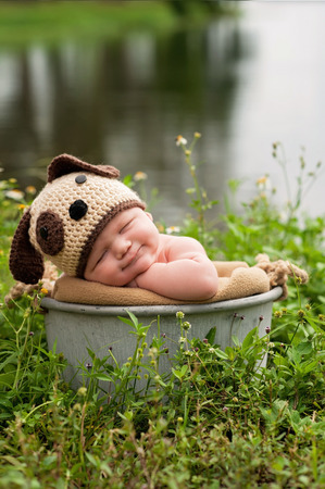 A smiling three month old baby boy wearing a crocheted puppy dog hat. He