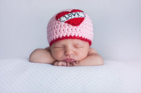 """saint valentin coeur: Portrait d'une vieille sept jours couchage b�b� fille portant un bonnet crochet� """"Love"""". Tir mignon � utiliser pour la Saint-Valentin"""