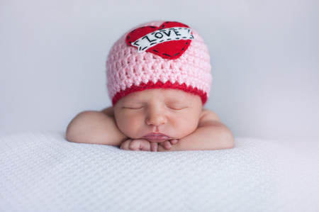 Portrait of a seven day old sleeping baby girl wearing a crocheted Love beanie. Cute shot to use for Valentine Stock Photo