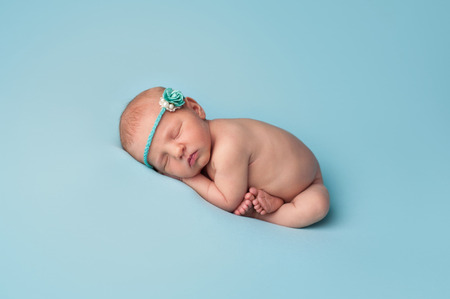 sleep: Portrait of a seven day old newborn baby girl. She is wearing a paper rose and pearl headband and is sleeping on light blue knit material. Stock Photo
