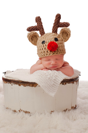 A smiling eight day old newborn baby boy wearing a red nosed reindeer hat and sitting in an antique wooden bucket. Photographed in a studio on a white background.
