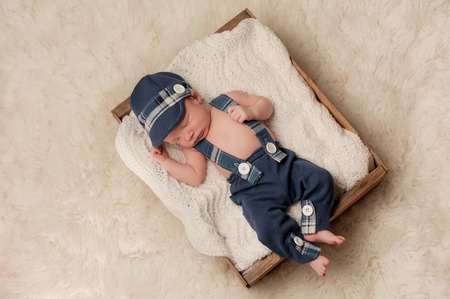 newsboy cap: Overhead shot of an eight day old newborn baby boy wearing a blue newsboy cap, suspenders and pants. He is sleeping in an old wooden crate. Shot in the studio on a cream colored flokati rug.