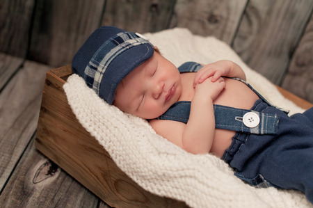 newsboy cap: An eight day old newborn baby boy wearing a blue newsboy cap, suspenders and pants. He is sleeping in an old wooden crate. Shot in the studio on a wooden background. Stock Photo