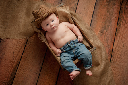 cowboy's: A four month old baby boy wearing a crocheted cowboy hat. He is lying in a wooden crate lined with burlap. Shot in the studio on a rustic, wood background.