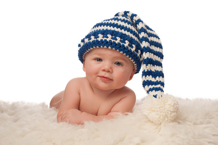 babies: A 4 month old baby boy wearing a blue and cream colored, crocheted stocking cap. He has a slight grin and is looking at the camera. Shot in the studio on a white background. Stock Photo