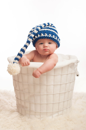 A 4 month old baby boy wearing a stocking cap. He is sitting in a wire basket with clenched fists and a pouting expression. Shot in the studio on a white background.