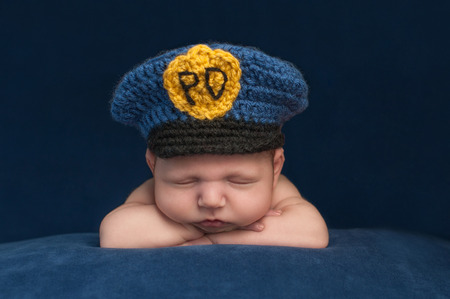 Twelve day old sleeping newborn baby boy wearing a blue crocheted police officer hat.