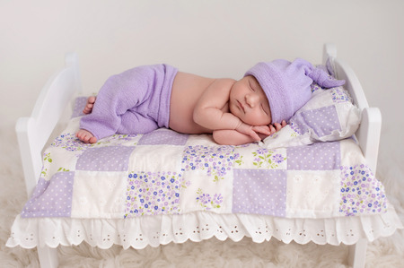 Nine day old newborn baby girl sleeping on a tiny white bed with pillow and patchwork quilt. She is wearing lilac colored pajamas with sleeping cap. Standard-Bild