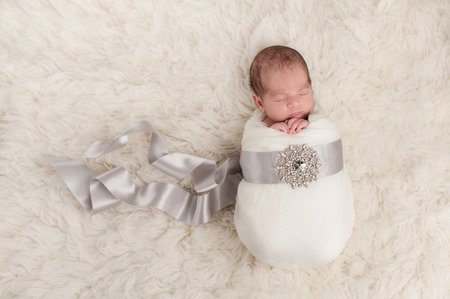 A sleeping nine day old newborn baby girl that is bundled up in a white swaddle, satin ribbon and rhinestone embellishment. She is lying on a while flokati (sheepskin) rug. Stock Photo