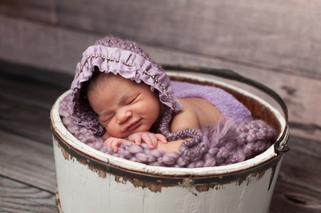 Eight day old newborn baby girl sleeping in a vintage, white wooden bucket. She is wearing a lilac colored knitted bonnet.