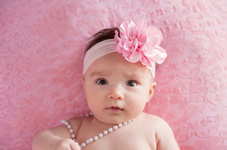 3 month: A portrait of an alert, 3 month old baby girl wearing a large, pink, flower headband and pearls. She is lying on her back on pink, lace material with a funny expression on her face. Stock Photo