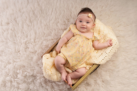 3 month: Smiling, three month old baby girl wearing a vintage inspired yellow, floral romper and lying in a yellow drawer.