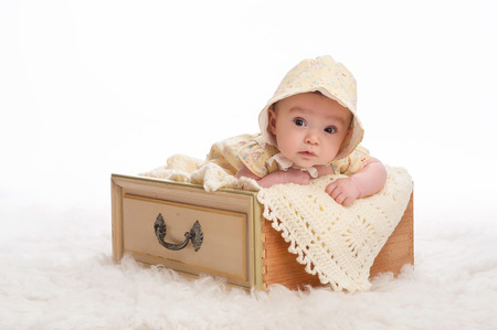 3 month: A 3 month old baby girl wearing a yellow bonnet and lying in a vintage yellow drawer.