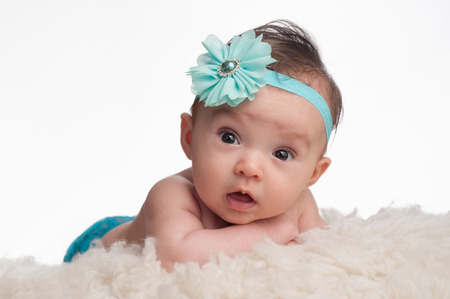3 month: A portrait of an alert, 3 month old baby girl wearing a turquoise blue flower headband. She is lying on her tummy, propped up on her forearms on a cream colored sheepskin rug.