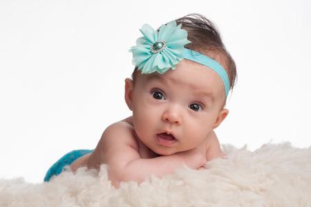cintillos: Un retrato de una alerta, 3 meses niña de bebé que llevaba un azul turquesa flor diadema. Ella está mintiendo en su panza, apoyado en sus antebrazos sobre una alfombra de piel de oveja de color crema.