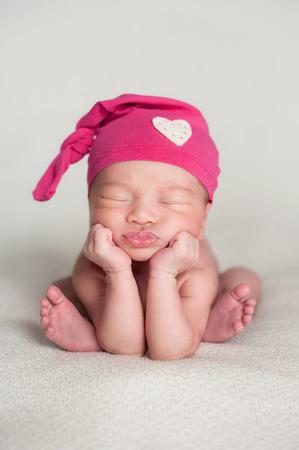 recien nacido: Un retrato de una hermosa once días de edad niña que lleva un casquillo top rosa upcycled nudo con detalle de corazón. Ella está durmiendo en una manta de color beige y posó con la barbilla er en sus manos.
