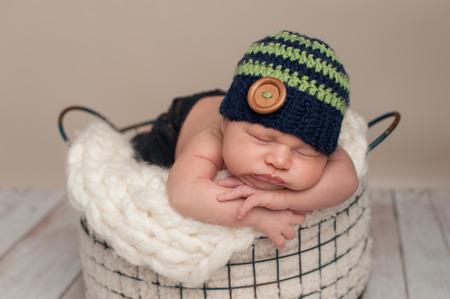 f8cc72c27 ... Tres semanas de edad bebé recién nacido con pantalones vaqueros y un  ganchillo azul y verde gorro. Él está durmiendo boca abajo en una cesta de  alambre.