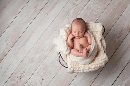 Un retrato de un bebé recién nacido que duerme siete días de edad en una cesta de alambre en un piso blanqueada, de madera.