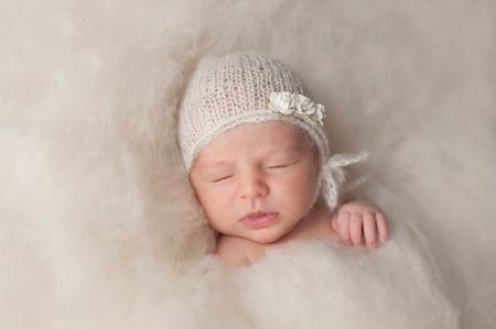 Een portret van een mooie zeven dagen oud pasgeboren baby meisje draagt een witte, gebreide, mohair bonnnet en steeg hoofdband. Ze slaapt in een bed van crèmekleurige wol batting.