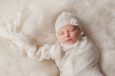 A portrait of a beautiful, seven day old newborn baby girl wearing a white, knitted, mohair bonnnet and rose headband. She is swaddled with a gauzy, white fabric and sleeping on cream colored wool batting.