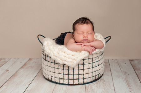 Three week old newborn baby boy wearing jeans and sleeping on his stomach in a wire basket. Shot in the studio on a whitewashed wooden floor.