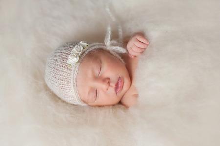 rosas blancas: Un retrato de un Bella joven de siete días de edad recién nacido niña llevaba un blanco, de punto, bonnnet mohair y se levantó la venda. Ella está durmiendo en una cama de color crema de bateo de lana. Foto de archivo