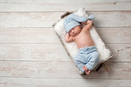 durmiendo: Bebé recién nacido durmiendo en una caja de madera en un suelo de madera encalada. Lleva azules, pijamas upcycled luz con una gorra a juego dormir. Foto de archivo