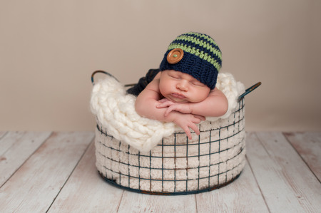 Three week old newborn baby boy wearing jeans and a crocheted blue and green beanie hat. He is sleeping on his stomach in a wire basket.